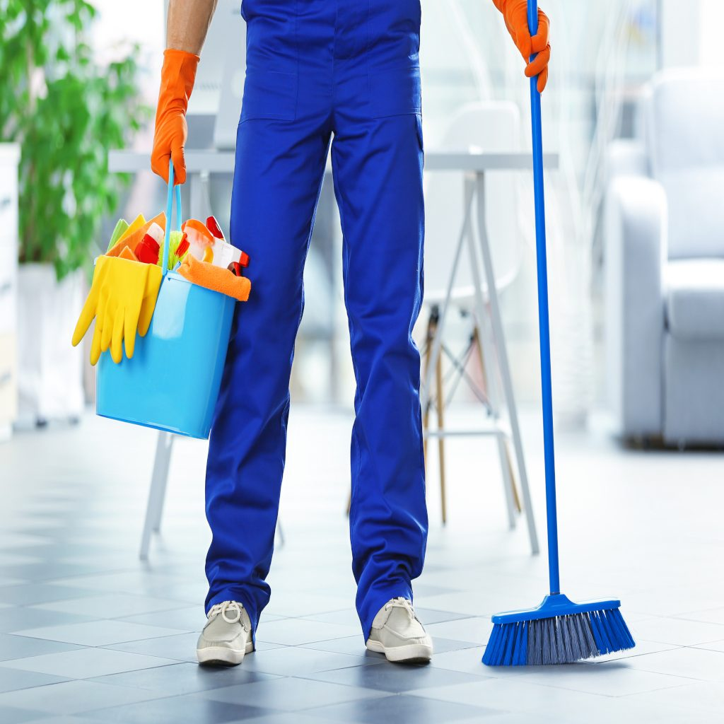 Young janitor holding cleaning products and tools in office